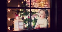 Little baby looking outside window in Christmas - Clarity Divorce