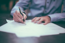 A man filling paper work - Clarity Divorce